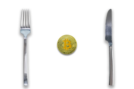 One Bitcoin crypto currency between fork and knife. Concept of Bitcoin scalability problem. Cryptocurrency market deficit and limitations. Isolated white background.