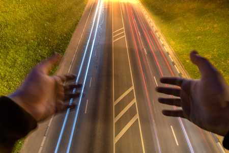 Male hands over night highway with car light streaks. Suicide concept. Long exposure photography. Copy space