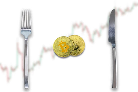 Two Bitcoins crypto currency between fork and knife. Concept of Bitcoin scalability problem. Cryptocurrency market deficit and limitations. Blurred trade chart going up background