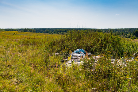 Unauthorized outdoor nature garbage dump in the summer field.