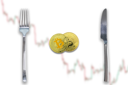 Two Bitcoins crypto currency between fork and knife. Concept of Bitcoin scalability problem. Cryptocurrency market deficit and limitations. Blurred trade chart going down background. 版權商用圖片