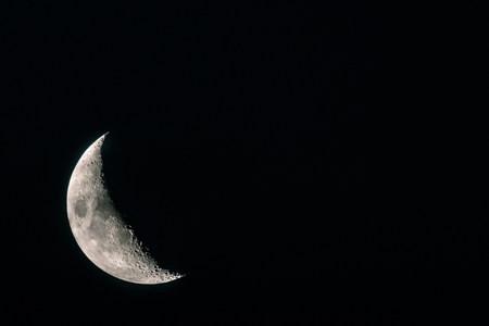 Half Moon grey close up. Astronomical body. Black deep cosmos space background. Copy space