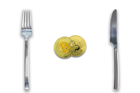 Two Bitcoins crypto currency between fork and knife. Concept of Bitcoin scalability problem. Cryptocurrency market deficit and limitations. Isolated white background.