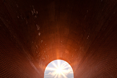 Arch of red brick. Sunlight at the end of tunnel. Symbol of hope, new life, search for goals and success. Imagens