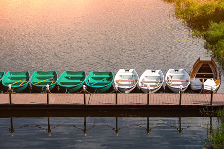 Pier with rowing boats for romantic river walk or fishing. Rowboats on the city river in downtown. Sunny atmosphere weather. Stock Photo