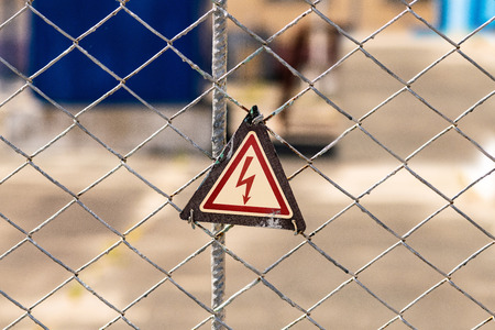 High voltage hazard warning sign on the fence. Power substation with environmentally friendly electrical technologies. Banque d'images