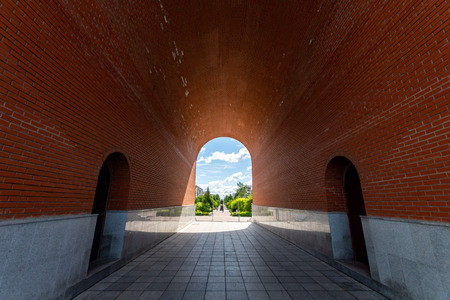 Arch of red brick. Sunlight at the end of tunnel. Symbol of hope, new life, search for goals and success. 免版税图像