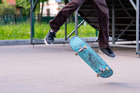 Skater boy performs a trick. Battered and scruffy skateboard. 写真素材