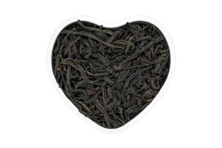 Lapsang souchong tea, heart-shaped, isolated, close up. Smoked Chinese Black Tea use for weight loss, caffeine alternative and improving heart health.