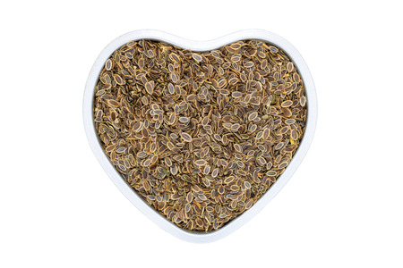 Dill seeds, heart-shaped, close up, isolated. Annual fennel herb used as spice in cooking or for pickling.