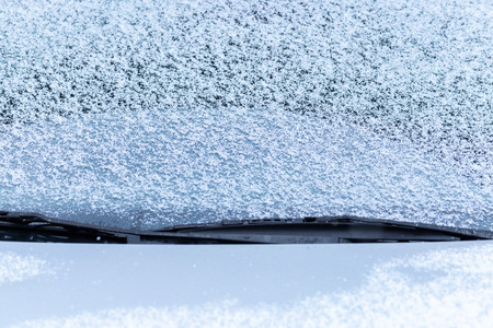 Snow covered car window with wipers, macro, close up. Antifreeze was not used. Vehicles in snow. Winter time is coming. Bad weather conditions
