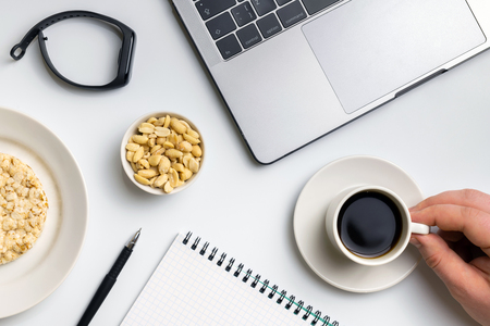 Healthy snacking at work during break time. Crispy rice rounds with peanuts, cup of coffee near the laptop, fitness-tracker and notebook. White organized desk. Imagens