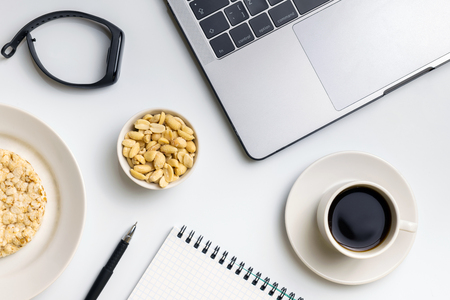 Healthy snacking at work during break time. Crispy rice rounds with peanuts, cup of coffee near the laptop, fitness-tracker and notebook. White organized desk. Foto de archivo