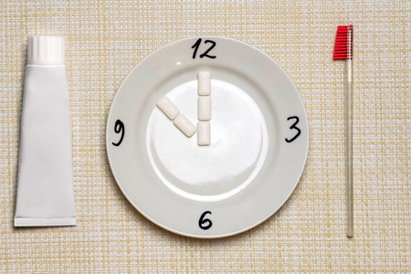 Teeth cleaning break concept. Time to your teeth brushing during work or eating. Clock symbol on plate. Teeth protect from tooth decay or plaque concept.