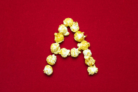 English alphabet from cinema popcorn. Letter A. Red background for design. Movie styling.