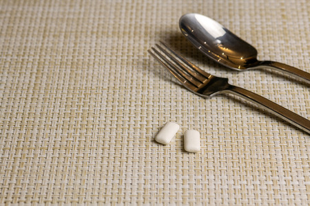 Chewing gums after eating to protect teeth from tooth decay or plaque. Sugar free oral hygiene during lunch or breakfast concept. Two gums, fork and spoon. Copy space. Foto de archivo