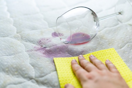 Cleaning wine stain with sponge. Spilled wine on white bed sheet. Dropped wineglass. Unlucky, unfortunate situation.