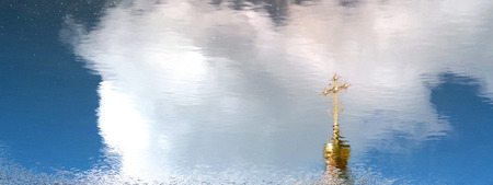 Golden dome and orthodox cross reflected in water surface. Blurred blue sky reflection in background. Copy space Banco de Imagens