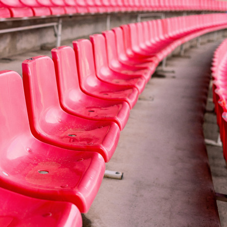 Red stadium seats after rain. Soccer, football or baseball stadium tribune without fans. End of the game.