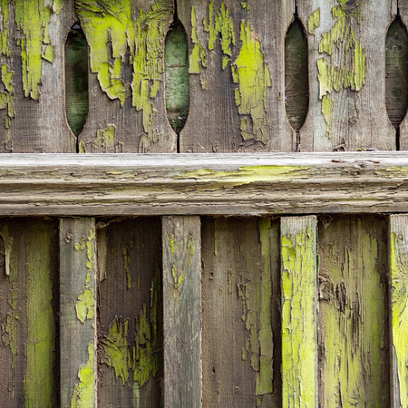 Old wooden fence soiled with peeling green paint. Abstract design background.