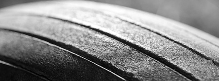 Old tread pattern for vehicle. Car wheel abrasion reduces safety. Close up black and white photo