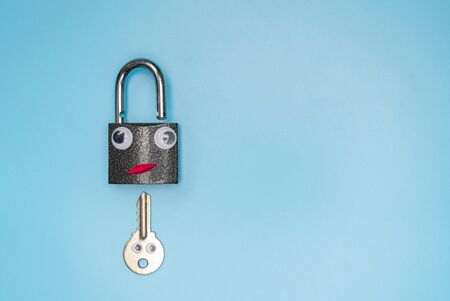Key and open lock sex dating or picking funny concept, copy space, blue background. Check the security system of your home or office.