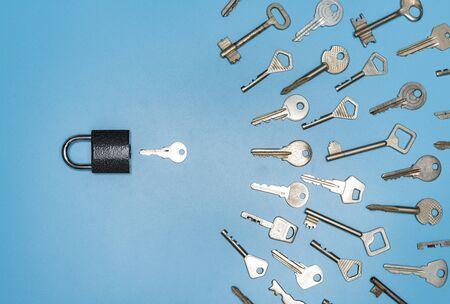Concepto de selección de llaves. Bloqueo y diferentes llaves antiguas y nuevas, fondo azul. Protección de negocio y casa, seguridad inmobiliaria.