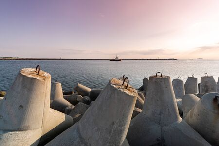 Tugboat sailing in sea to tow ship to port. Tetrapod breakwaters in harbor. Beautiful sunset over the pier. Stock fotó