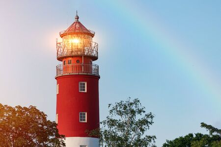 Lighthouse in Baltiysk port. Beautiful rainbow and beacon lights. Clean blue sky, copy space.