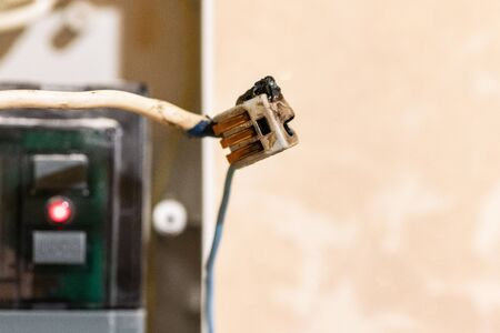 Burned wire, splicing connector, electrical terminal block of nonflammable, fireproof material. Faulty wiring or negligent electrical work. Dangerous short circuit accident.