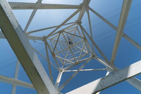 Transmission tower, view from below. Overhead pylon power line tower, distribution and transmit electrical energy across large distances. Banque d'images - 130757486