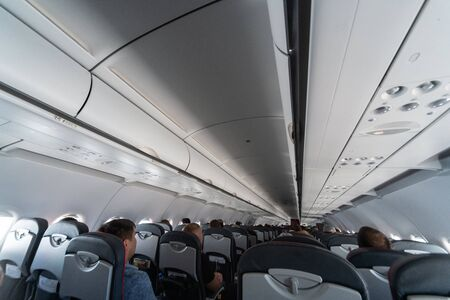 Airplane cabin seats with passengers. Economy class of new cheapest low-cost airlines without delay or cancellation of flight. Travel trip to another country. Standard-Bild