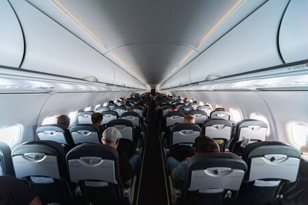 Airplane cabin seats with passengers. Economy class of new cheapest low-cost airlines without delay or cancellation of flight. Travel trip to another country.