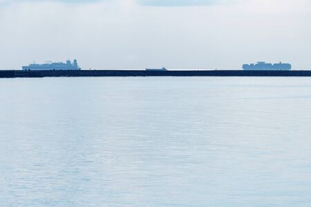 Seascape with cargo ships on horizon. Coastline in bay. Ships carry freight containers, fishing and park.