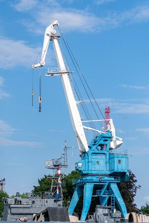 Repair crane in shipyard. Reconstruction old naval ship or unloading cargo ashore. Waiting for ship parts