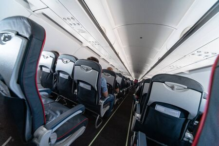 Airplane cabin seats with passengers. Economy class of new cheapest low-cost airlines. Travel trip to another country. Turbulence in flight.