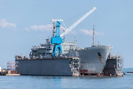Large iron navy ships in shipyard for repair. Big crane in dockyard. Blue sea harbor