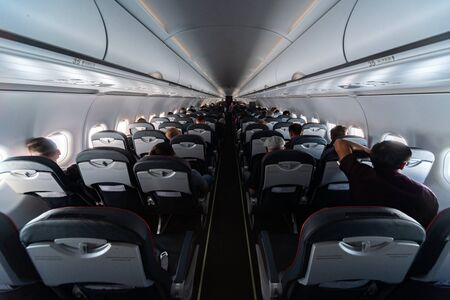 Airplane cabin seats with passengers. Economy class of new cheapest low-cost airlines without delay or cancellation of flight. Travel trip to another country. Foto de archivo