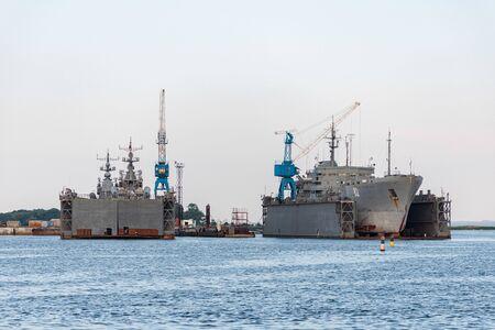 Large iron navy ships in shipyard for repair. Big crane in dockyard. Blue sea harbor 版權商用圖片