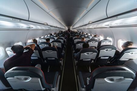 Airplane cabin seats with passengers. Economy class of new cheapest low-cost airlines without delay or cancellation of flight. Travel trip to another country. 写真素材