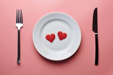 Due cuori in piatto con posate. Cena romantica nel concetto di ristorante. Incontro di innamorati al ricevimento di nozze.