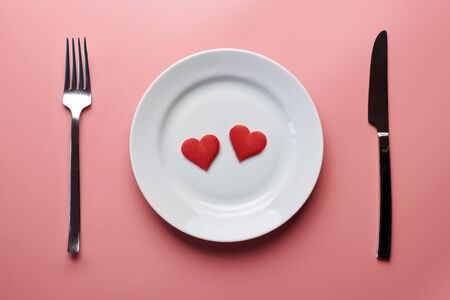 Zwei Herzen im Teller mit Besteck. Romantisches Abendessen im Restaurantkonzept. Treffen der Liebenden bei der Hochzeitsfeier.