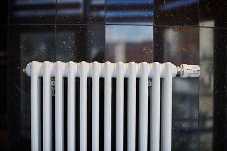 Heating radiator in office, close up. White heat exchangers. Iron aluminium steam radiator. Pipe pattern.