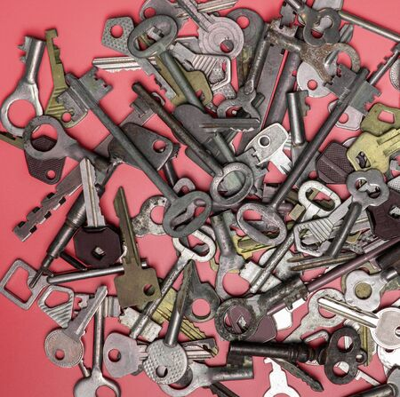 Keys set on pink background. Door lock keys and safes for property security and house protection. Different antique and new types of keys. Banque d'images