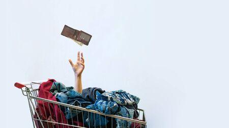 La mano femminile sporge dal carrello pieno di vestiti. Concetto di shopping. Shopping incontrollabile - disturbo dell'acquisto compulsivo o oniomania. Copia spazio. Archivio Fotografico