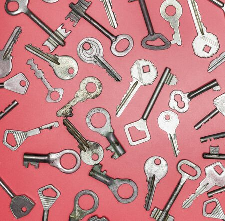 Keys set on pink background. Door lock keys and safes for property security and house protection. Different antique and new types of keys. Stock Photo