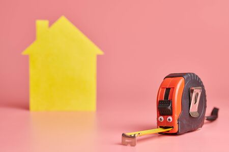 House renovation funny concept. Metal tape measure and other repair items. Home repair and redecorated concept. Yellow house shaped figure on pink background. 写真素材