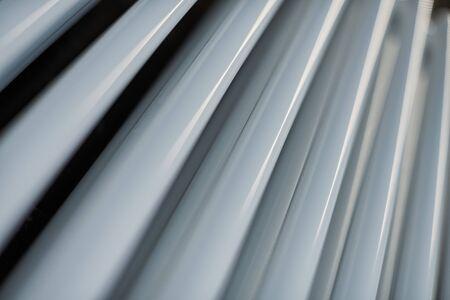 Heating radiator in office, close up. White heat exchangers. Iron aluminium steam radiator. Pipe pattern. 写真素材