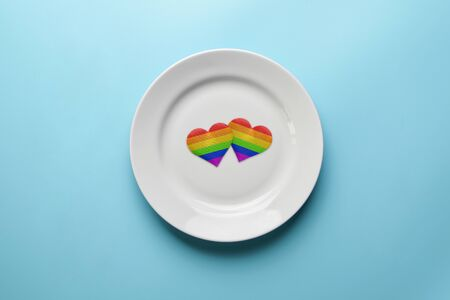 Two hearts in LGBT flag colors in plate. Romantic gay community dating. Dinner without discrimination against sexual minorities. LGBT wedding banquet preparation.