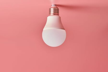 Energy saving light bulb, copy space, pink background. Minimal idea concept.